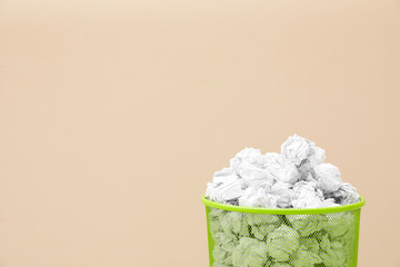 Metal bin with crumpled paper against color background, space for text