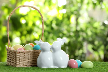 Cute ceramic Easter bunnies with wicker basket and dyed eggs on green grass against blurred background, space for text