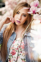 Close up portrait of beautiful blonde woman posing near the blooming magnolia flower tree outdoors.