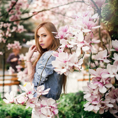 Outdoor portrait of young sensual blonde woman in jeans jacket posing near beautiful Magnolia flower tree in the garden on blooming season. Spring time
