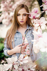 Young attarctive blonde woman in jeans jacket posing near beautiful Magnolia flower tree on blooming season. Spring time