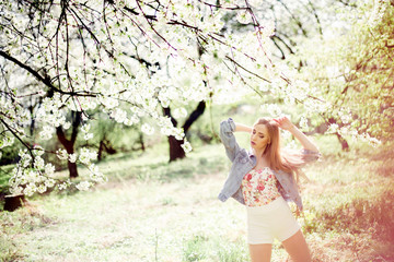 Young beautiful girl in stylish outfit posing under blooming tree in the spring garden on sunny day