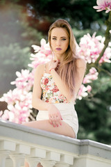 Young attarctive blonde woman posing near beautiful Magnolia flower tree on blooming season. Spring time in the park