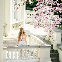 Beautiful young woman with long blonde hair standin on the terrace near the blooming Magnolia flower tree in the park or garden. Sunny spring day