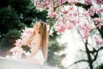 Young sensual blonde woman posing near beautiful Magnolia flower tree on blooming season. Spring time in the park. Rear view