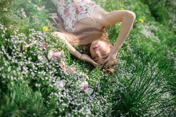 Young sensual blonde woman lying on the green grass with flowers in the park on sunny summer day