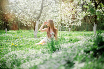 Young sensual blonde woman sitting on the green grass with flowers and blooming trees in the park on sunny spring day