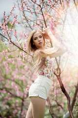 Young attractive blonde woman in bright clothes posing near the blooming magnolia flower tree in the park. Spring blooming season
