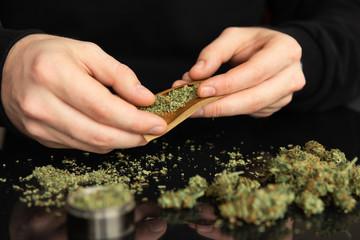 Man rolling a marijuana weed blunt. Close up of addict lighting up marijuana joint with lighter.