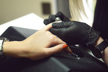 Shellac removal. The master makes a manicure. Relaxing day at beauty salon. Manicurist master makes manicure on woman's hand. Girl nails, color gel nail Polish finger in nail salon training.Spill nail