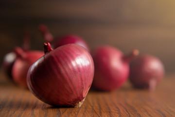 Fresh purple onions on dark wooden background.