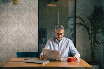 active senior man reading newspaper and drinking coffee in restaurant