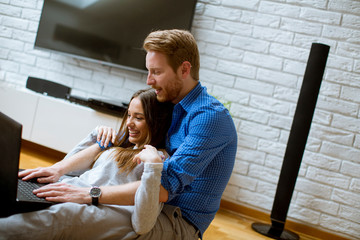 Close up of a couple using a notebook while sitting on the floor in their living room