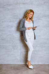 Young woman standing witd digital tablet by wall