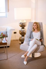 Young woman at home sitting on modern chair and reading book