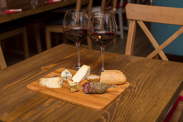 Red wine and assorted cheese plate with sausage