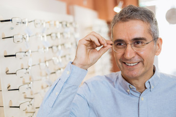 portrait of senior man wearing glasses in optic store
