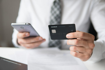 Online trading on the currency exchange. Smartphone and Internet Commerce. Online payments through the phone. Young businessman with a bank credit card in his hands. Payment of goods online.
