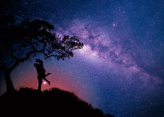 Milky Way with couple  under the tree on the hill. Landscape with night starry sky and silhouette of standing happy man and woman hugging in starry sky. Milky way with travelers,copy space.