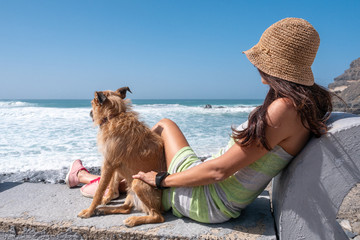 young girl with her dog watching the sea