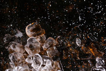 Ice on colored glass, black background and golden glitter. A concept of beautiful texture.