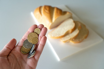 Fototapeta The coins in the woman's hand over the white table on which the sliced ​​fresh bread lies, demonstrates the lack of money for food