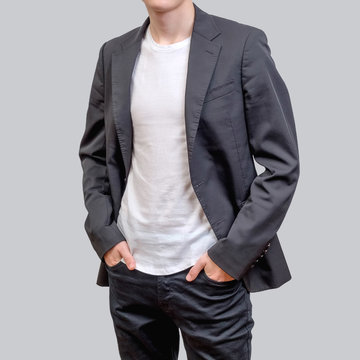 Trendy young man wearing grey blazer and dark jeans, standing against a grey background.