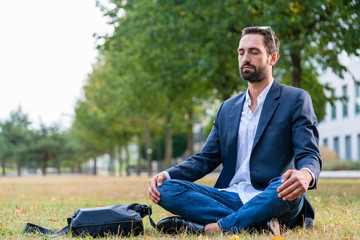 Relaxed businessman doing meditation in the park