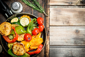 Assortment of grilled vegetables with a pan of herbs and spices on a cutting Board.