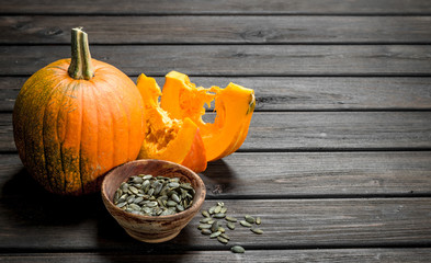 Pumpkin seeds in a bowl and pieces of ripe pumpkin.