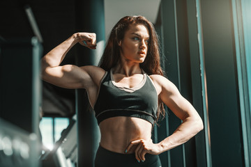 Portrait of beautiful Caucasian female bodybuilder posing in gym and showing muscles. Don't wish for it, work for it.