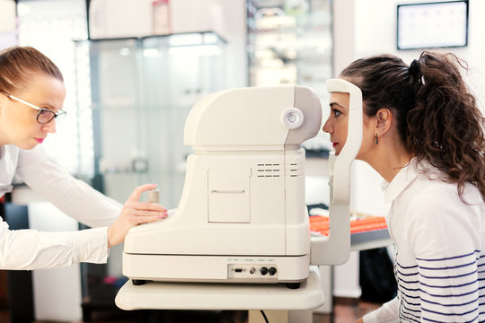 Woman sitting on chair at ophthalmologist and checking eyesight. Female doctor using autorefractor.