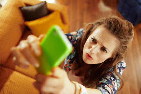 concerned fit woman catching weak wifi signal on smartphone