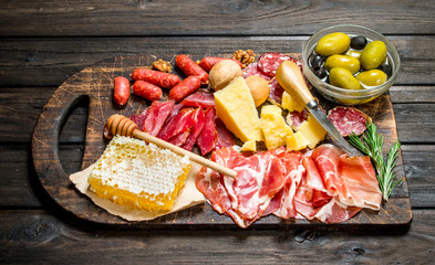 Antipasto background. Assortment of meat snacks on the Board with olives and Parmesan.