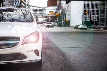 Close up of side of a white luxury vehicle parked on the street in the city, light beam on, North America