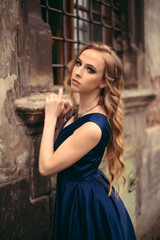 Portrait of young beautiful blonde woman in gorgeous blue long dress posing on the streets of the old city.