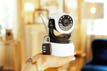 Closeup on wifi security camera and lock in hand of housewife Wall mural