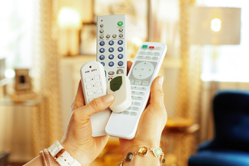Closeup on remote controls in hands of modern woman