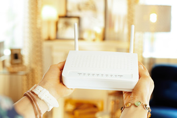 Closeup on modern wifi router with 2 antennas in hand of woman