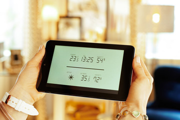 Closeup on smart home weather station in hands of housewife