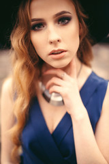 Close up portrait of beautiful young woman with gorgeous make up, necklace in blue dress and hat posing at the camera outdoors.