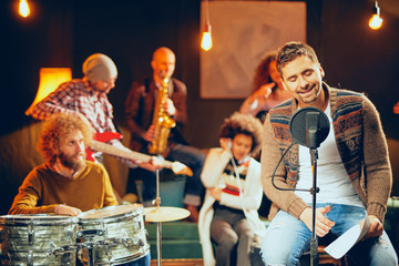 Man singing and sitting on chair while his band playing instruments in background. Home studio interior.