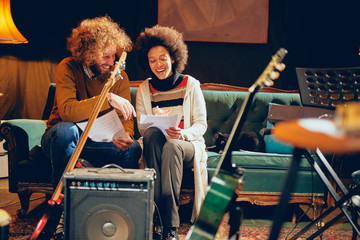 Mixed race woman sitting on the sofa with her Caucasian friend and looking at notes in home studio.