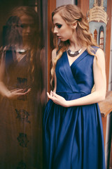 Young sensual woman in gorgeous long blue dress standing near the window in the cafe.