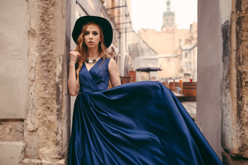 Portrait of beautiful young blonde woman in gorgeous long blue dress and black hat standing near the old building wall in the city street.