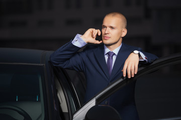 Young businessman in dark blue suit calling on cell phone leaning on his car