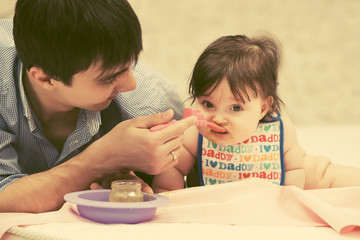 Happy young father feeding baby girl on blanket at home