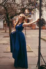 Young attractive blonde woman in long blue dress posing in the old city street.