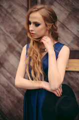 Young beautiful blonde woman in long blue dress posing in the old city street near the wooden wall