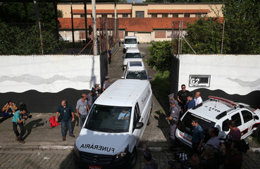 Funerary vehicles with bodies leave the Raul Brasil school after a shooting in Suzano